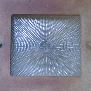 Molded flower in glass light cover, on the west side entrance